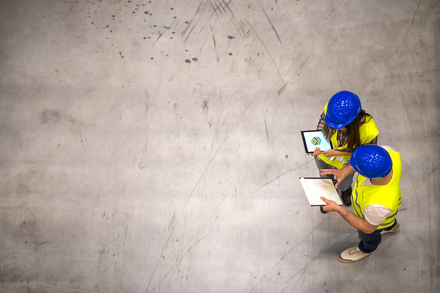 top-view-of-two-industrial-workers-wearing-hardhats-and-reflective-jackets-holding-tablet-