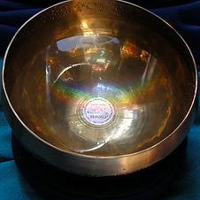 Klangschale mit Wasser und Spiegelung eines Regenbogens als Cover zu Sound Healing Aura Reinigung