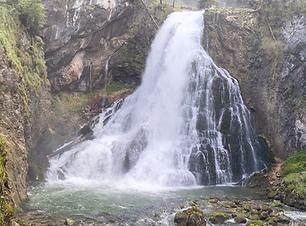 Ein Wasserfall vor hohen Felsen als Cover für Naturaufnahme & Klangschalen Sound Healing Waterfall