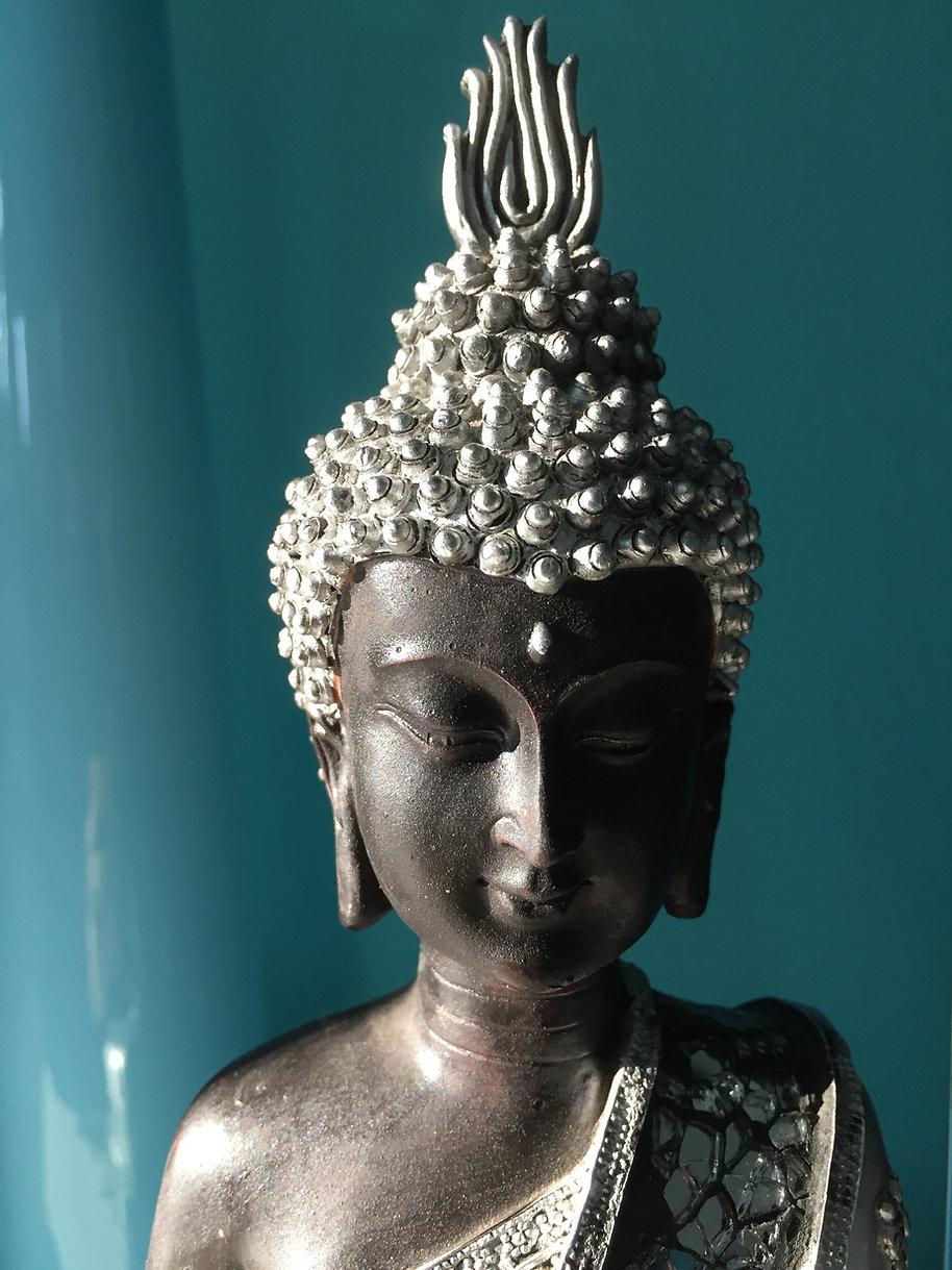 Der Kopf einer silberfarbenen meditierenden Buddha Statue als Hintergrundbild für die Referenzen und Erfahrungen zu den Klangschalenmeditationen von Sound of Healing Arts, Klangmeditationen, Reality Creation und mehr von Petra Schilske