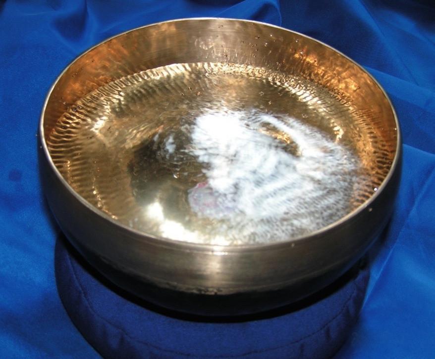 Bronzefarbene Klangschale auf einem königsblauem Tuch mit einem Wasserklangbild das wie ein Engel aussieht