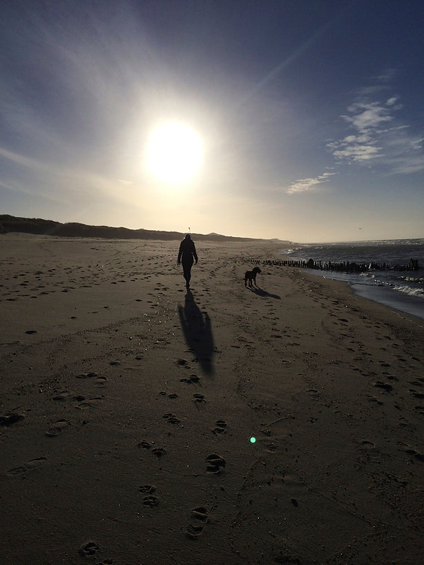 Petra Schilske und ihr Hund am Meer als Einladung zu Klangmeditation, Reality Creation und mehr