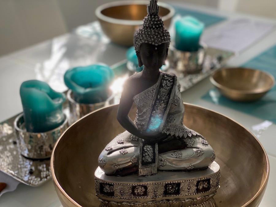 Ein Buddha sitzt in meditiver Haltung tief ruhend einer Klangschale