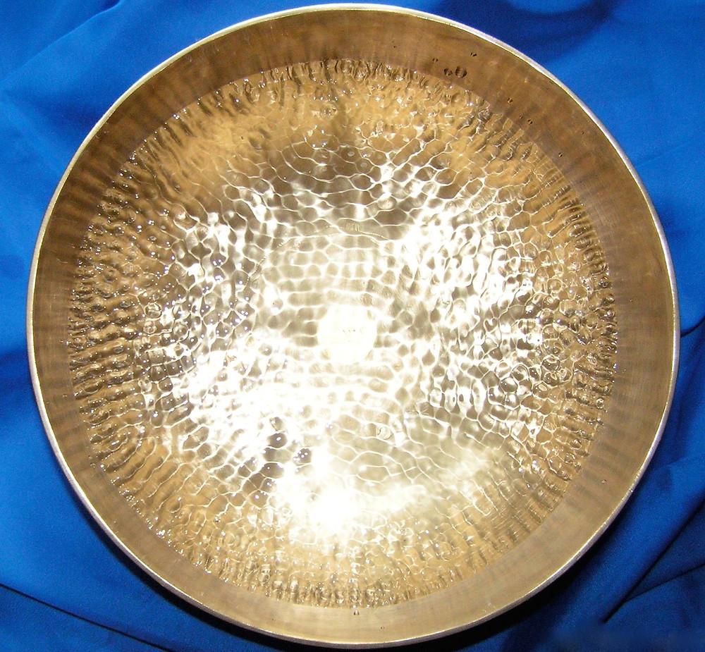 Ein wie eine strahlende, goldene Sonne aussehendes Wasserklangbild in einer großen Messingklangschale auf einem blauen Tuch