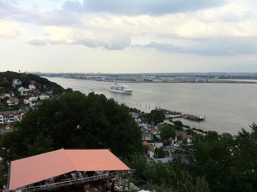 Ein großes Passagierschiff verlässt den Hamburger Hafen Richtung Nordssee, von einem Hügel aus aufgenommen