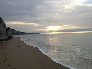 Felsenküste und Meer bei Sonnenuntergang als Cover für die Klangschalen pur & Meer Normandie