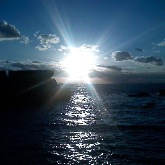 Die Sonne über Felsen und dem Meer als Cover für die Klangmeditation Reality Creation