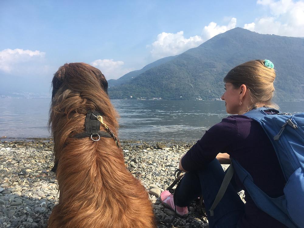 Mit Grisou und mit dem Rücken zur Kamera am Steinstrand vom Lago Maggiore sitzend, im Hintergrund Berge, Wolken und der blaue Himmel
