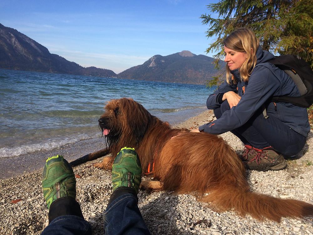Mit Hund und Mann am Kiesstrand des Walchensees vor einer Bergkulisse