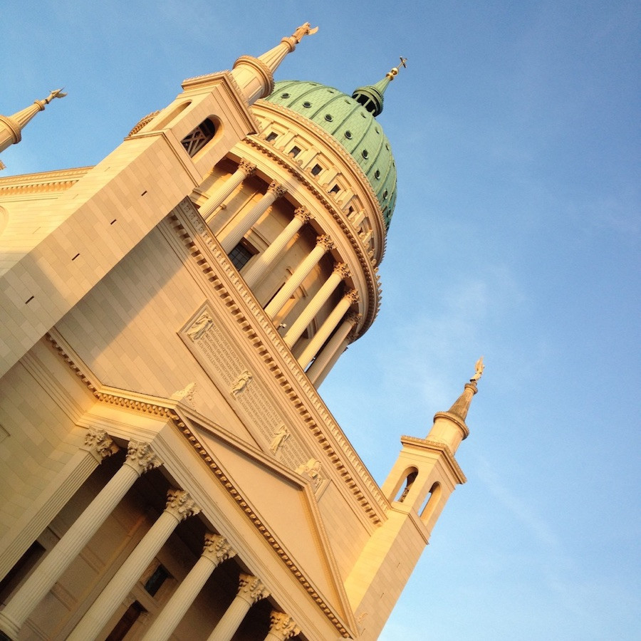 Die Nikolaikirche aus gelben Sandstein in Potsdam vor einen stahlend blauen Himmel schräg fotografiert, so dass es schein, sie würde umstürzen.