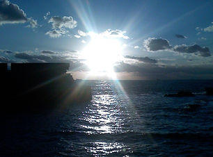 Sonnenuntergang vor blauem Himmel über dem Meer als Cover für die Klangmeditation Reality Creation