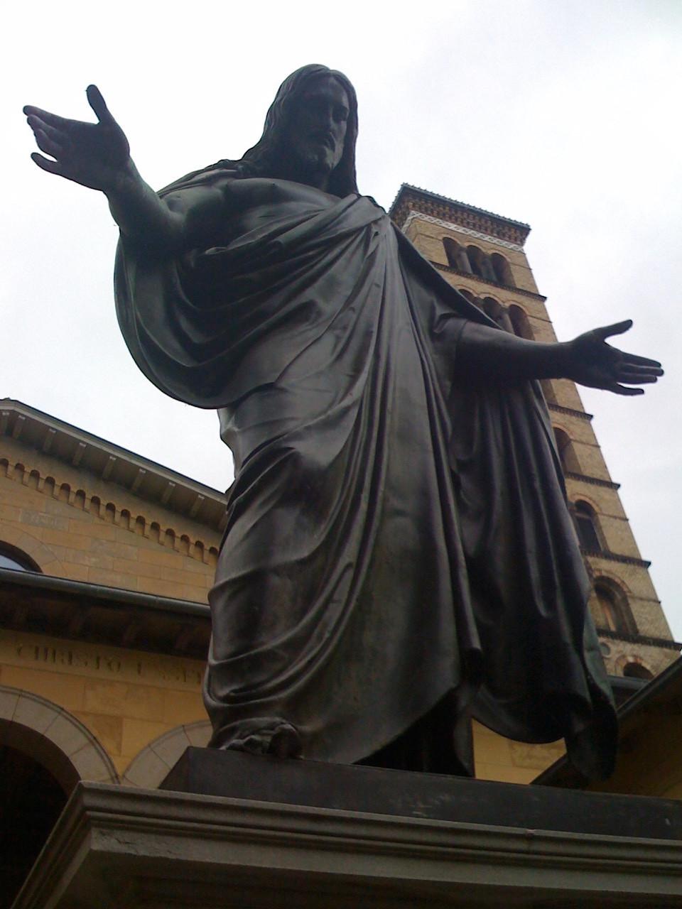 Eine große Statue von Jesus mit ausgebreiteten Armen von unten aufgenommen