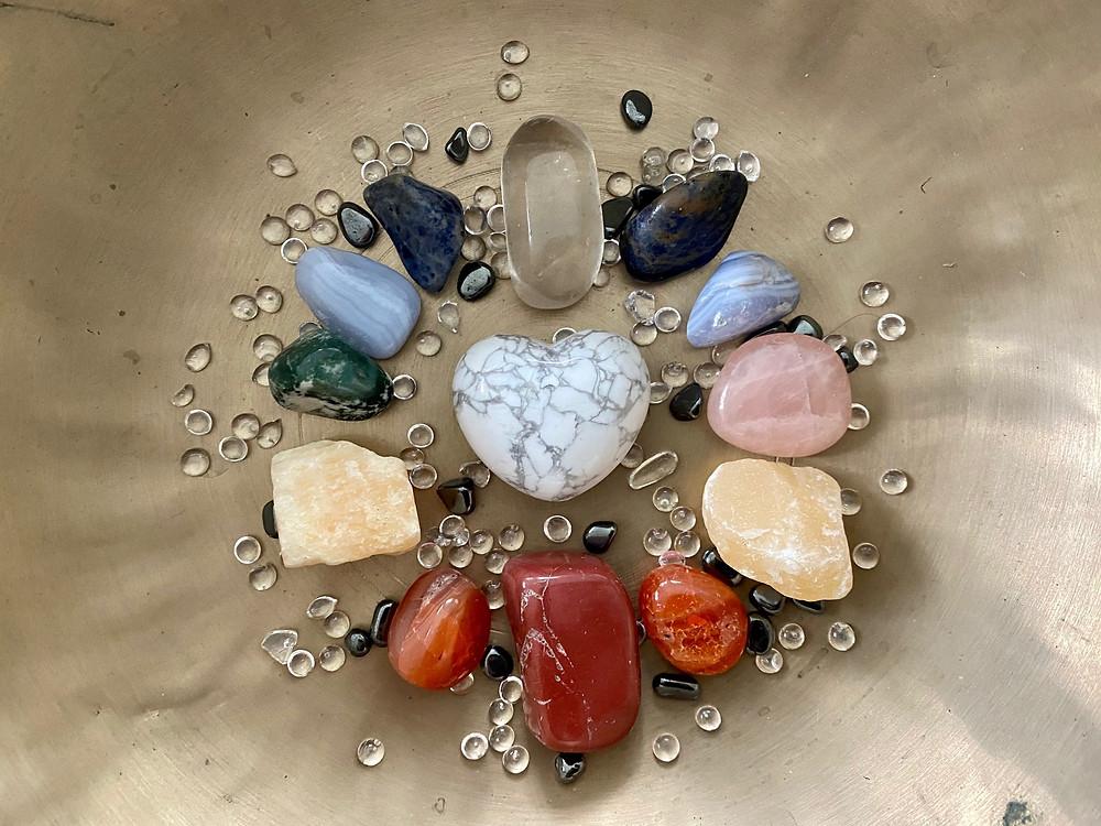 Farblich zu den Chakren passende Edelsteine im Kreis um ein Herz aus Stein am Boden einer Klangschale für die Klangmeditation Chakra Heilung