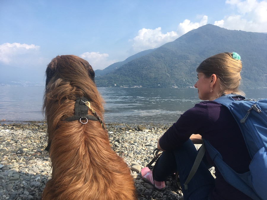Mein Hund und ich sitzen am Lago Maggiore mit Blick auf den See als Symbol für stimmiges im Hier und Jetzt sein und die Kraf der Gegenwart.