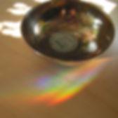Silberne Klangschale auf Holzfussboden mit Regenbogen Licht