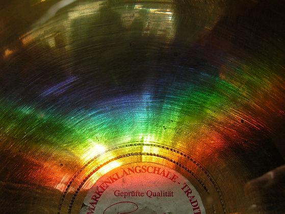 Der Boden einer Klangschale mit Regenbogen aus Licht als Cover für die Klangmeditation Wurzelchakra