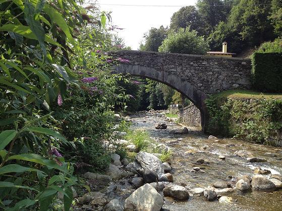 Eine alte Steinbrücke über einem Fluss als Cover für die Naturaufnahme Der Fluss Sanagra am Comer See