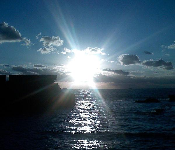 Blauer Himmel mit Sonne und Sonnenstrahlen über dem Meer zum Text über das Thema Reality Creation und Schöpfer sein.