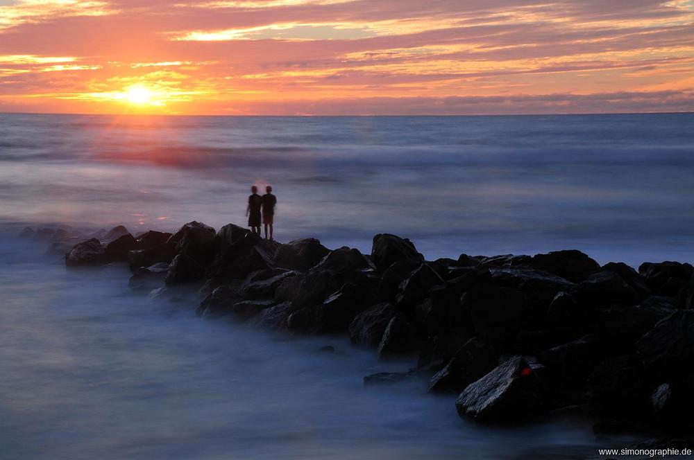 Zwei Menschen stehen auf Felsen, die ins Meer münden und schauen in einen vom Sonnenuntergang beschienenen Horizont