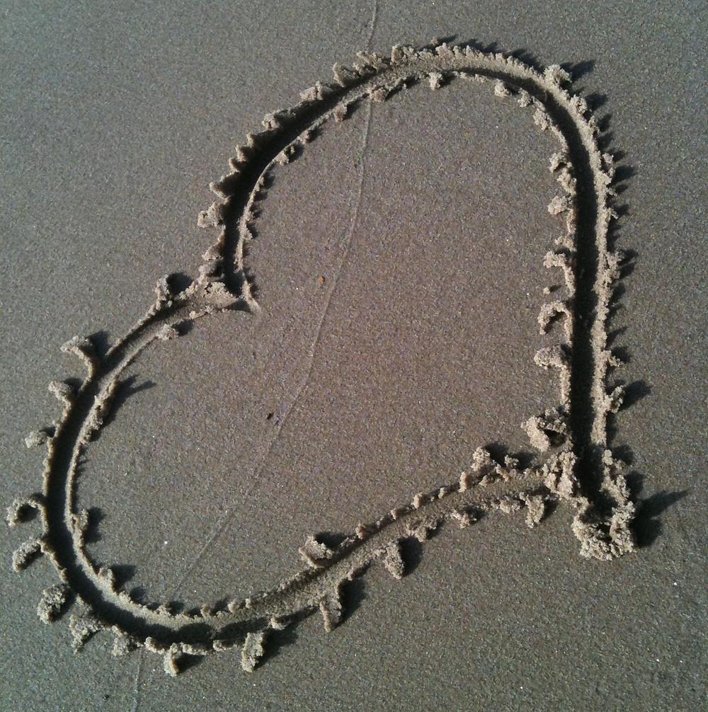 Ein in den Sandstrand gezeichnetes Herz