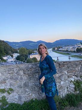 Petra Schilske von Sound of Healing Arts, im Hintergrund die Stadt Salzburg mit Bergen und Fluss