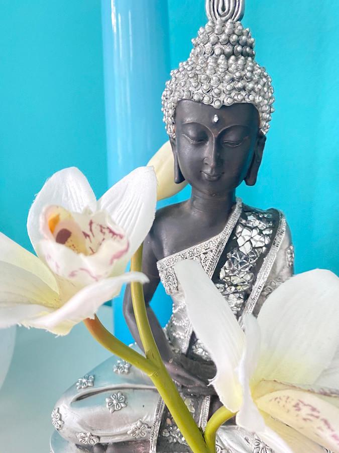 Ein sitzender, silberner Buddha vor blauem Hintergrung mit einer weißen Orchidee vor sich
