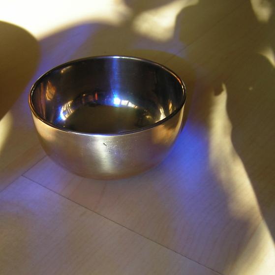 Silberne Klangschale in lilafarbenem Licht als Cover für die Klangmeditation für die Augen