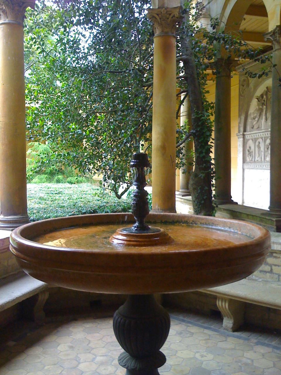 Ein alter kleiner Springbrunne von Säulen umgeben mit Blick ins Grüne