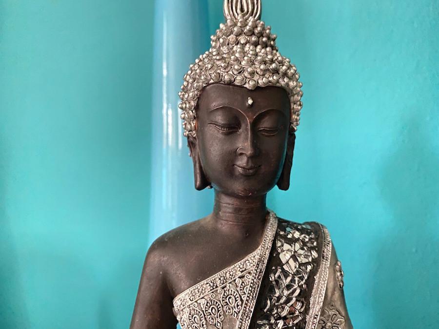 Silberner Buddha -  Statue vor einem türkisfarbenen Hintergrund