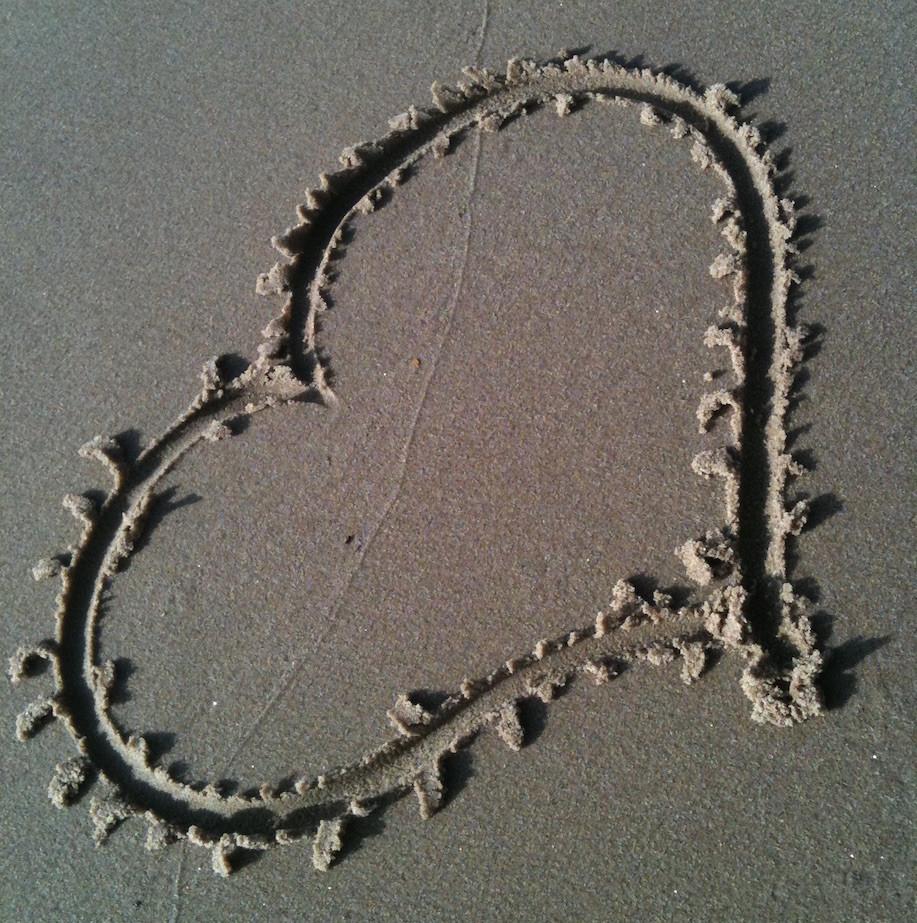 Ein in den Sand gezeichnetes Herz als Symbol dafür, dass Deine Schwingung das Tool für Dein Leben ist.