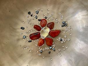 Dunkelorangefarbende Edelsteine und ein Bergkristall zur Aktivierung und Heilung des Sakralchakras