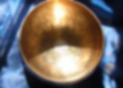 Bengali Klangschale im Sonnenlicht auf einem dunkelblauen Tuch