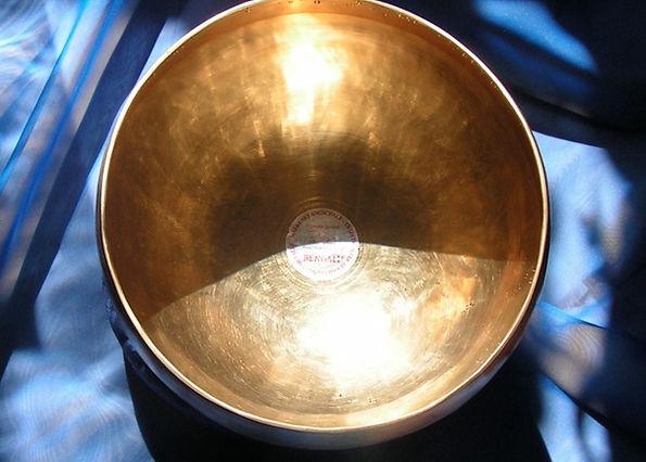 Bengali Klangschale im Sonnenlicht auf einem dunkelblauen Tuch als Foto für meine älteren Klangschalenmeditationen