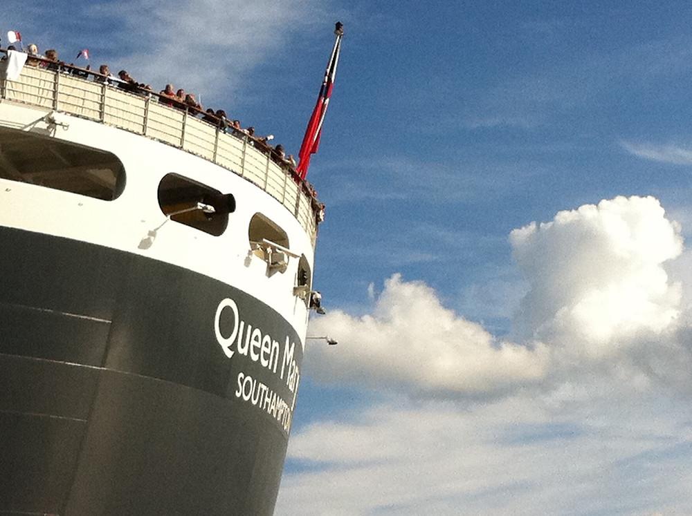 Das Heck der Queen Mary vor einem blauen Himmel mit weißen Schäfchenwolken bei Ihrer Abfahrt im Hafen von Hamburg