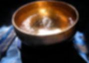 Von der Sonne beschienene Bengali Klangschale mit Wasser gefüllt und angeschlagen auf einem blauen Tuch