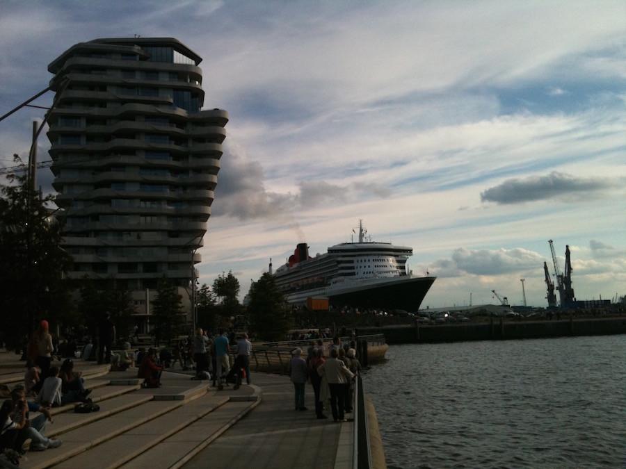 Ein sehr großes Passagierschiff beim Wendemanöver im Hamburger Hafen, daneben ein Hochhaus zum Größenvergleich