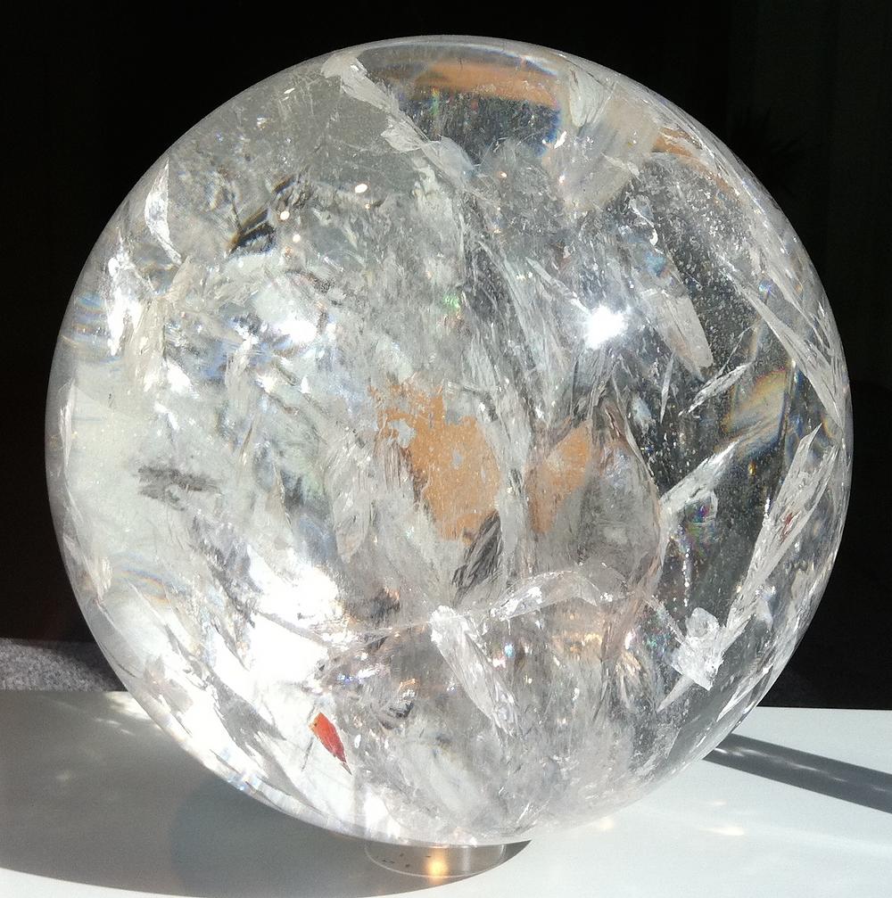 Eine große Bergkristallkugel vor einem schwarzen Hintergrund