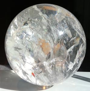 Eine Kugel aus Bergkristall auf einem weißen Tisch vor einem schwarzen Hintergrund