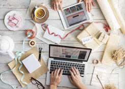 Schreibtisch mit Nähutensilien und Laptops