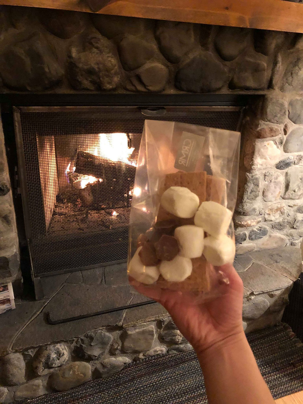 Canadian winter smores chocolate marshmallows by wood burning fireplace. winter travel blog activities.