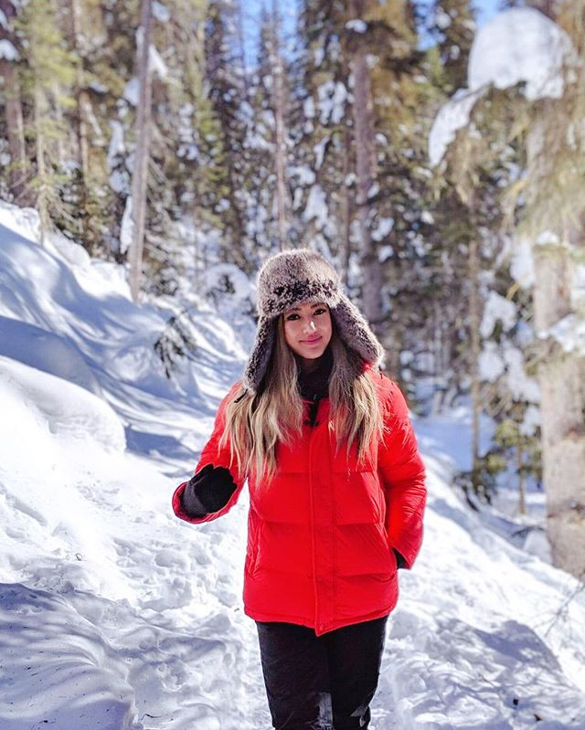 Girl travel blogger hiking in beautiful Canadian Rockies Mountain in the winter time. Frozen lakes and rivers and trees. Winter outfit.