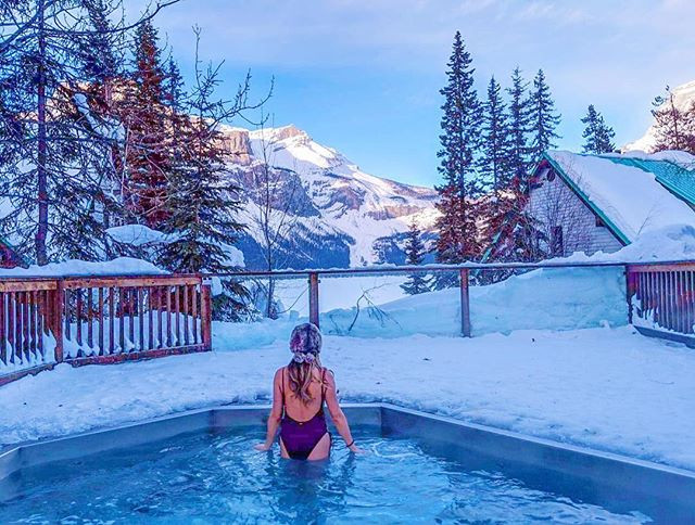 photograph of peaceful winter holidays. travel to emerald lake lodge in beautiful canadian rocky mountains with frozen lake in lake louise. Hot tub swimsuit winter time.
