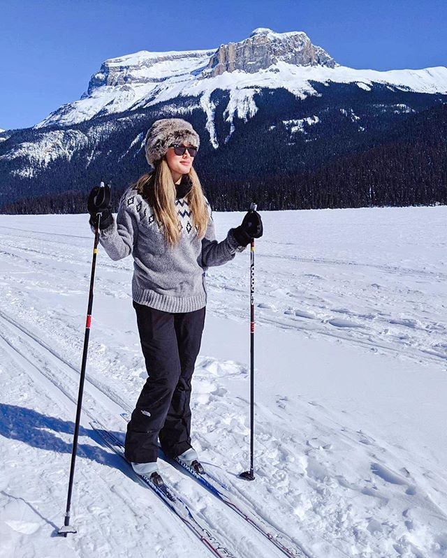 Girl travel writer fashion blogger cross-country skiing in the Rockies Mountains in yoho national park. Frozen winter at Emerald Lake Lodge. Banff. Ray Bans winter sport. Vegan winter outfit.