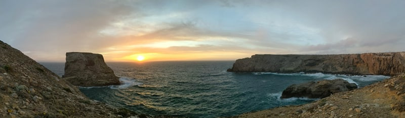Gorgeous panoramic photograph of portugal coastline. Girl travel blogger watching gorgeous sunset.