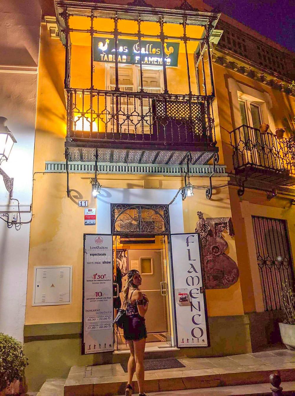 Photo of girl travel blogger entering flamenco bar in seville spain. los gallos flamenco dance performance.