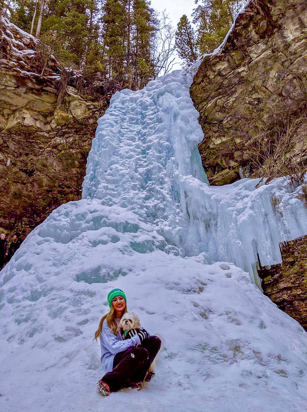 Photograph of travel girl with cute shihtzu in front of frozen glacier waterfalls in Canadian Rocky mountains in Canada.