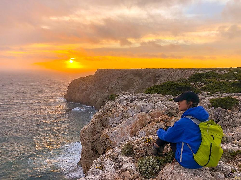 Girl travel blogger hikes Portugal. Enjoys the gorgeous sunset in Cape St. Vincent. Listen to the Ocean. Coastline. Beach. Waves. Girl Blogger. Travel Blog.