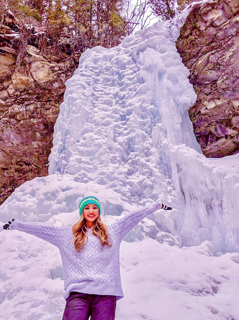 Photograph of happy girl travelling to see frozen glacier waterfall in Canadian rocky mountains, located in Kananaskis Alberta in Canada during wintertime.