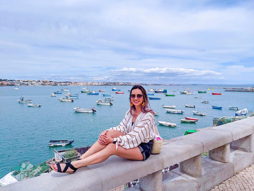 Photograph of girl travel fashion blogger in boating outfit in beautiful Old TownCascais Marina in Portugal with sailboats and yachts.
