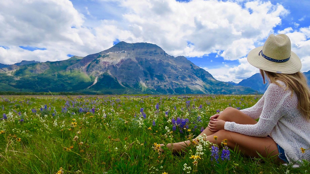 Girl travel blogger explores Waterton Lakes National Park in Canada and enjoys the wildflower festival in a meadow of wild flowers in the middle of the Rocky Mountains.